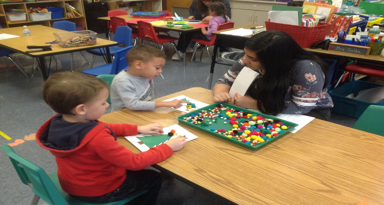High School Students working with preschool students.
